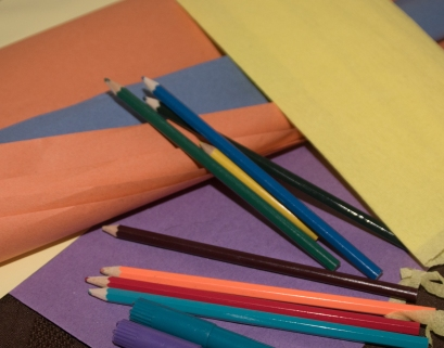 colouring pens and paper lying on a table